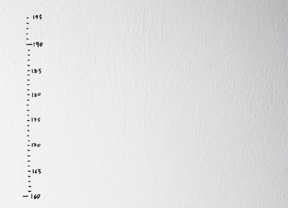 Height measurement chart on a white wall.