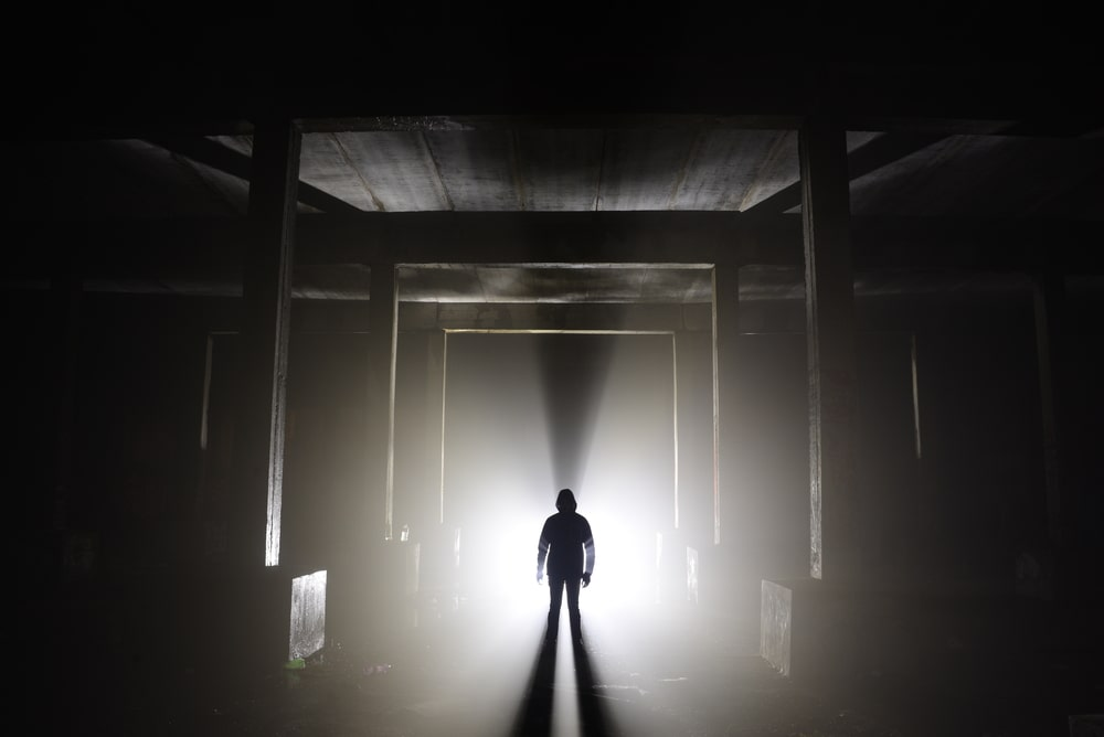 Silhouette of a person in an abandoned hallway.