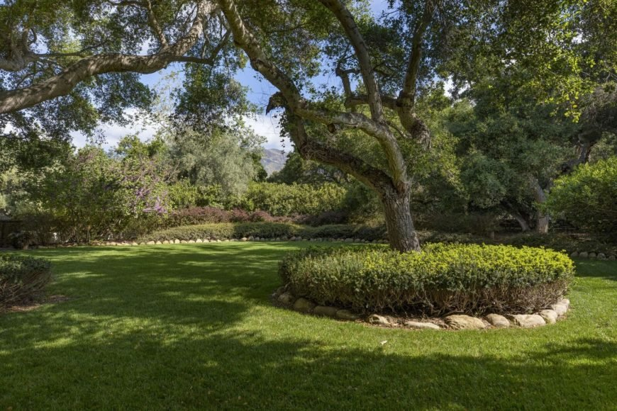 A view of the lush garden with perfectly-maintained lawn and beautiful green plants along with healthy mature trees. Images courtesy of Toptenrealestatedeals.com.