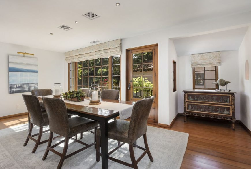 The dining room features a rectangular dining table set paired with stylish chairs on top of an area rug covering the hardwood flooring. Images courtesy of Toptenrealestatedeals.com.