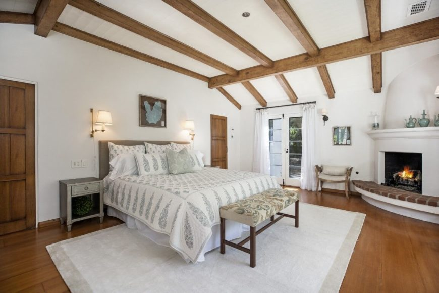 The master bedroom boasts a large comfy bed and has a fireplace set in the corner. The room features hardwood floors and a tall ceiling with wooden beams. Images courtesy of Toptenrealestatedeals.com.