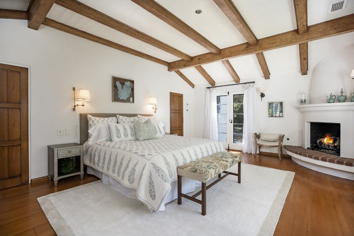 The primary bedroom boasts a large comfy bed and has a fireplace set in the corner. The room features hardwood floors and a tall ceiling with wooden beams. Images courtesy of Toptenrealestatedeals.com.