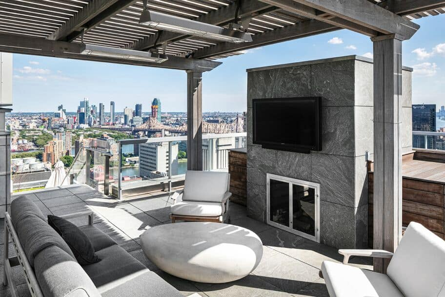 There's an outdoor living space set on the home's rooftop, offering a modern sofa set and a fireplace along with a widescreen TV set in front. Images courtesy of Toptenrealestatedeals.com.