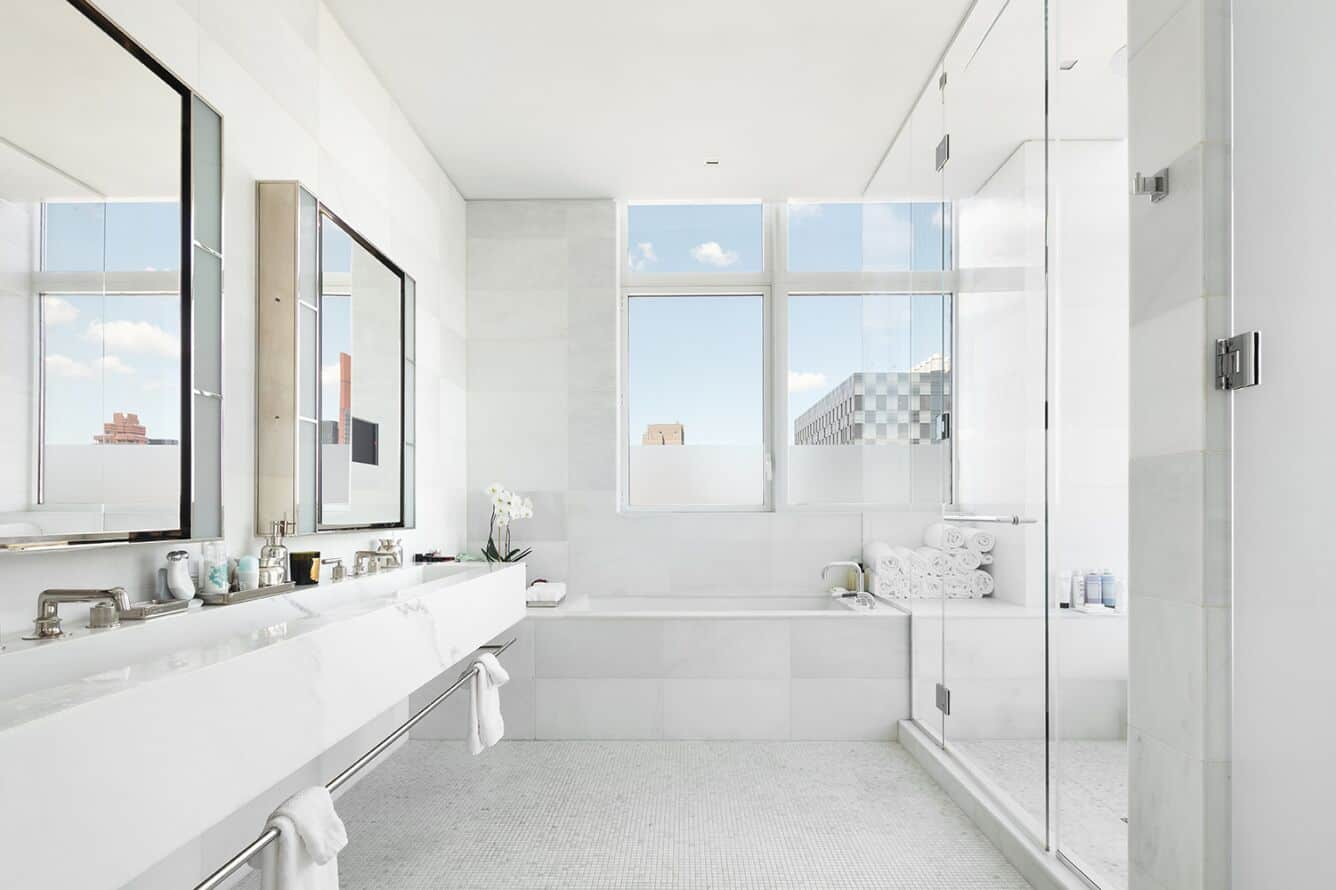 The bathroom boasts a drop-in deep soaking tub, along with a large walk-in shower room anda white floating vanity with two large sinks. Images courtesy of Toptenrealestatedeals.com.
