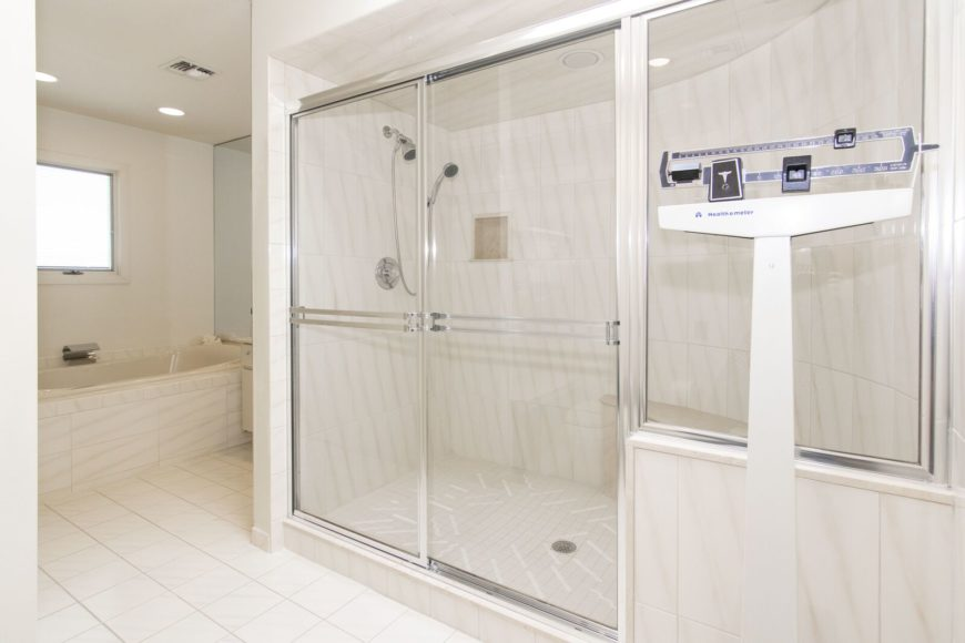 The home's primary bathroom offers a walk-in shower room and a drop-in deep soaking tub. There's a weighing scale in the room as well. Images courtesy of Toptenrealestatedeals.com.