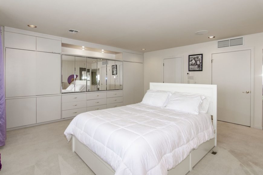 This bedroom suite features a cozy bed set in the middle. The room features mirrors on the wall along with carpeted flooring. Images courtesy of Toptenrealestatedeals.com.