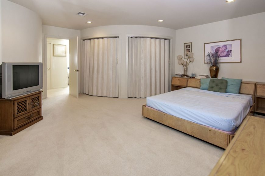 One of the mansion's bedroom suites featuring a nice comfy bed and carpeted flooring. Images courtesy of Toptenrealestatedeals.com.