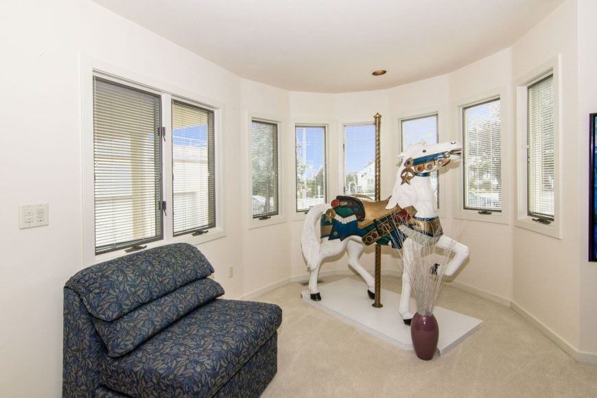 A sitting area featuring a comfortable seat near the windows, along with a single horse carousel decor. Images courtesy of Toptenrealestatedeals.com.