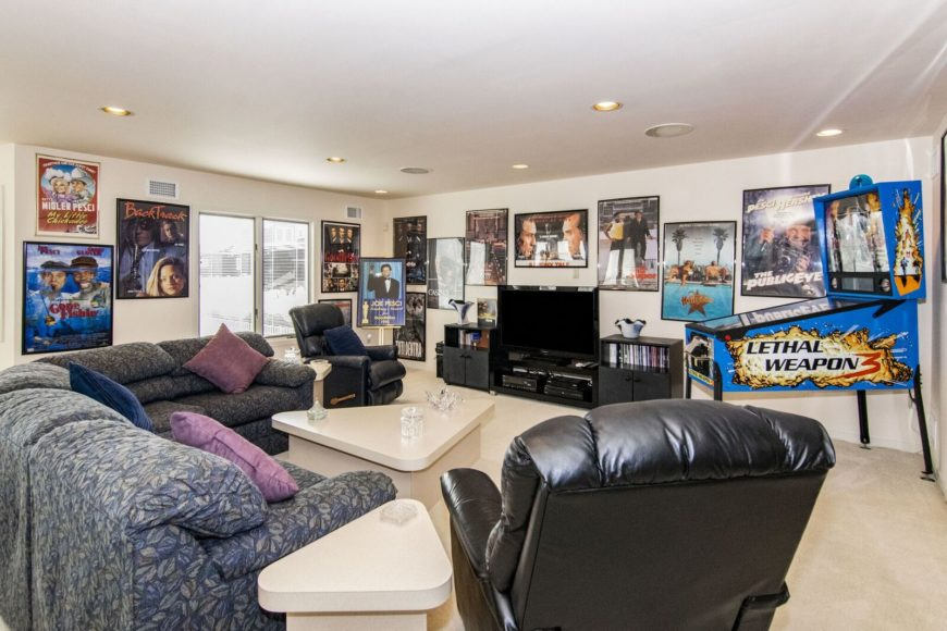 A nice family room boasting comfy seats and a stylish center table. The area is surrounded by framed movie posters wall decors and a widescreen TV in front. Images courtesy of Toptenrealestatedeals.com.
