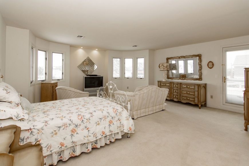 The primary bedroom offers a small living space set with a widescreen TV in front, along with a classy-looking bed set. The room has a doorway leading to the balcony and a personal bathroom as well. Images courtesy of Toptenrealestatedeals.com.