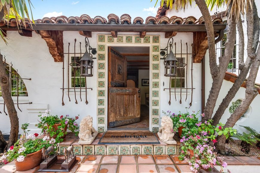 A doorway leading through the home's indoor amenities, surrounded by lovely plants and exterior home decors. Images courtesy of Toptenrealestatedeals.com.