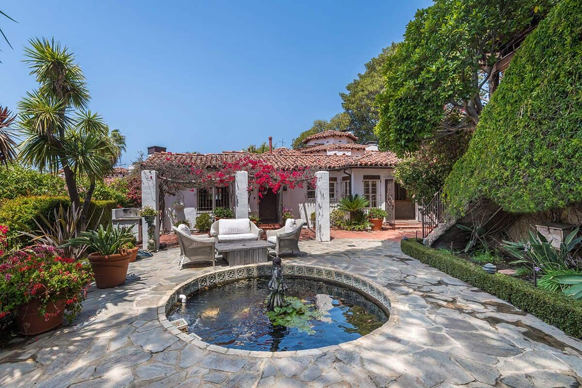 John Barrymore's Mansion With Opium Den. It has a gorgeous backyard boasting healthy plants and trees, along with beautiful outdoor amenities.