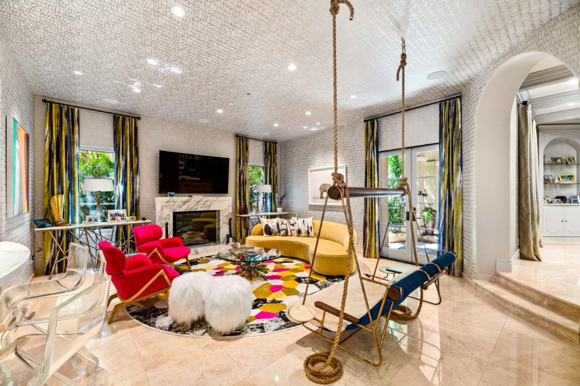 Another view of Kaley Cuoco's family living set with a charming set of seats and a a fireplace, along with a flat-screen TV on the wall. The area has a stunning ceiling lighted by recessed ceiling lights. Images courtesy of Toptenrealestatedeals.com.