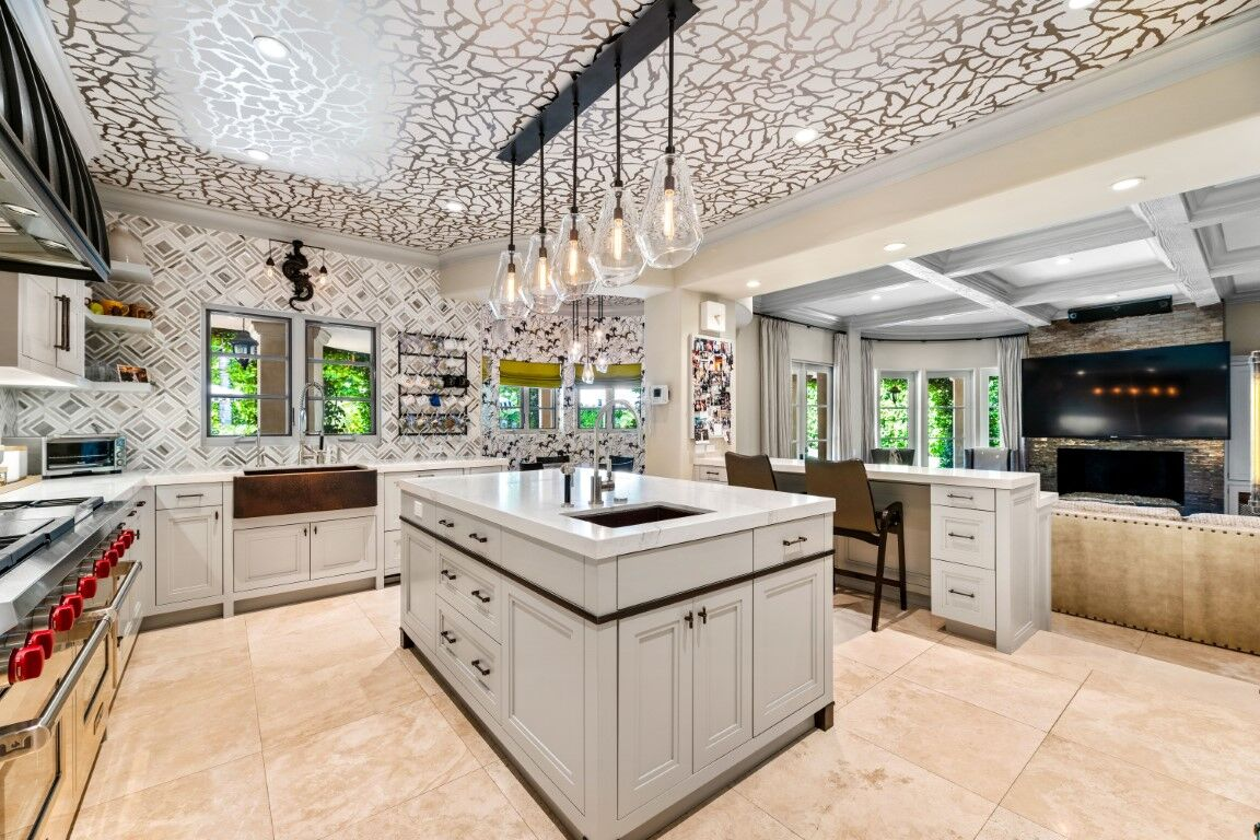 This kitchen boasts stylish walls and backsplash, along with a jaw-dropping ceiling design. There's a center island with a thick marble countertop lighted by classy pendant lights. Images courtesy of Toptenrealestatedeals.com.
