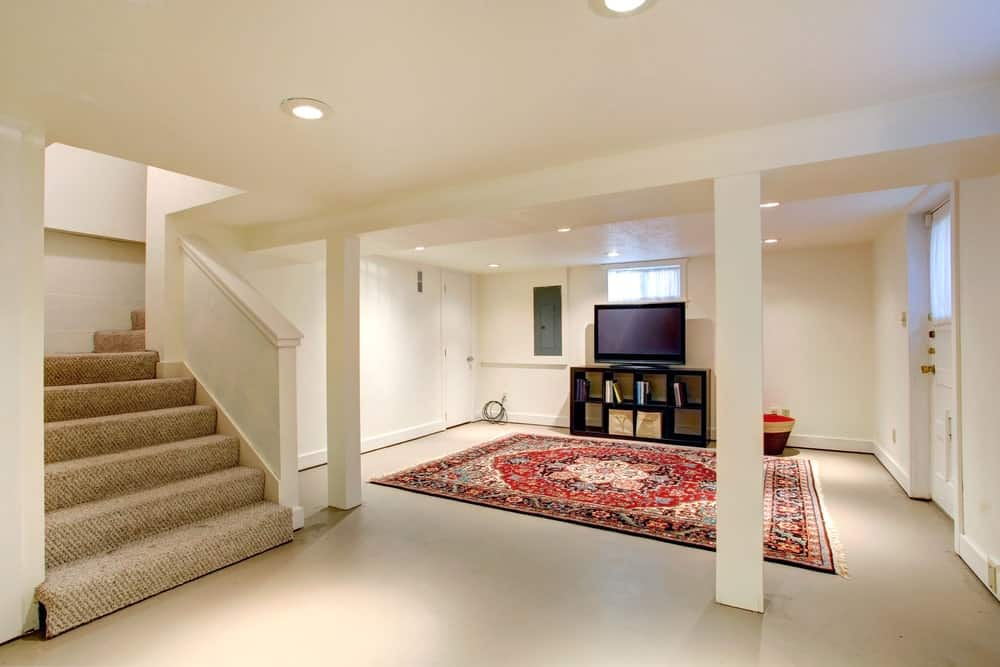 A large and modish basement with white walls and ceiling. It also has a large area rug and a TV stand with multiple shelving. There's a widescreen TV as well.