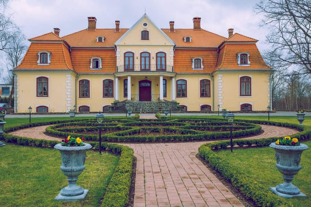 An old manor house in Latvia with a yellow exterior and orange roof. It courtyard and garden look so peaceful and beautiful.