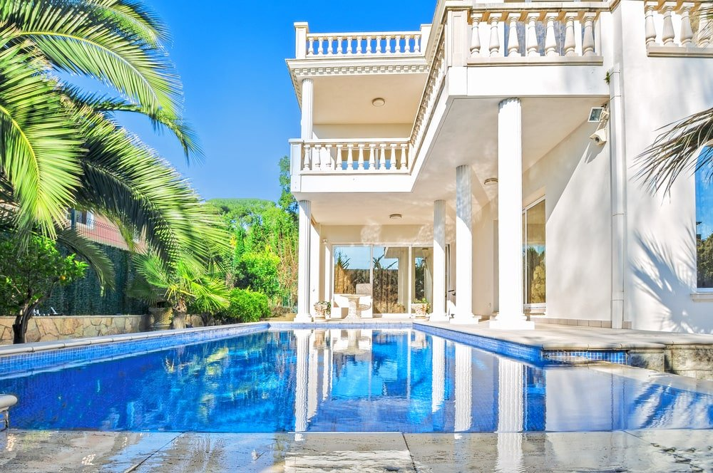 Luxury white house with a swimming pool.