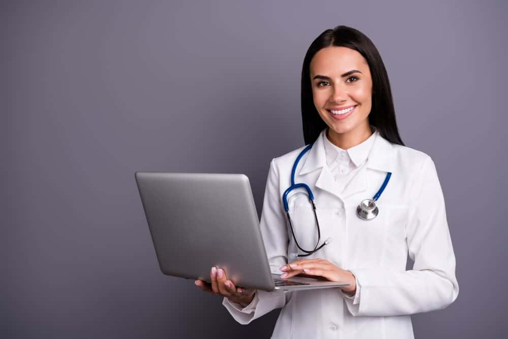 A medic woman holding a laptop.