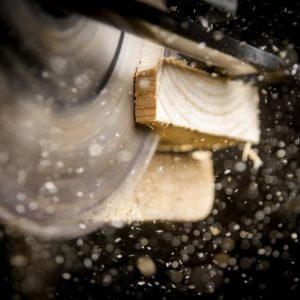 A close-up shot of a circular saw cutting a piece of wood with a dark background.