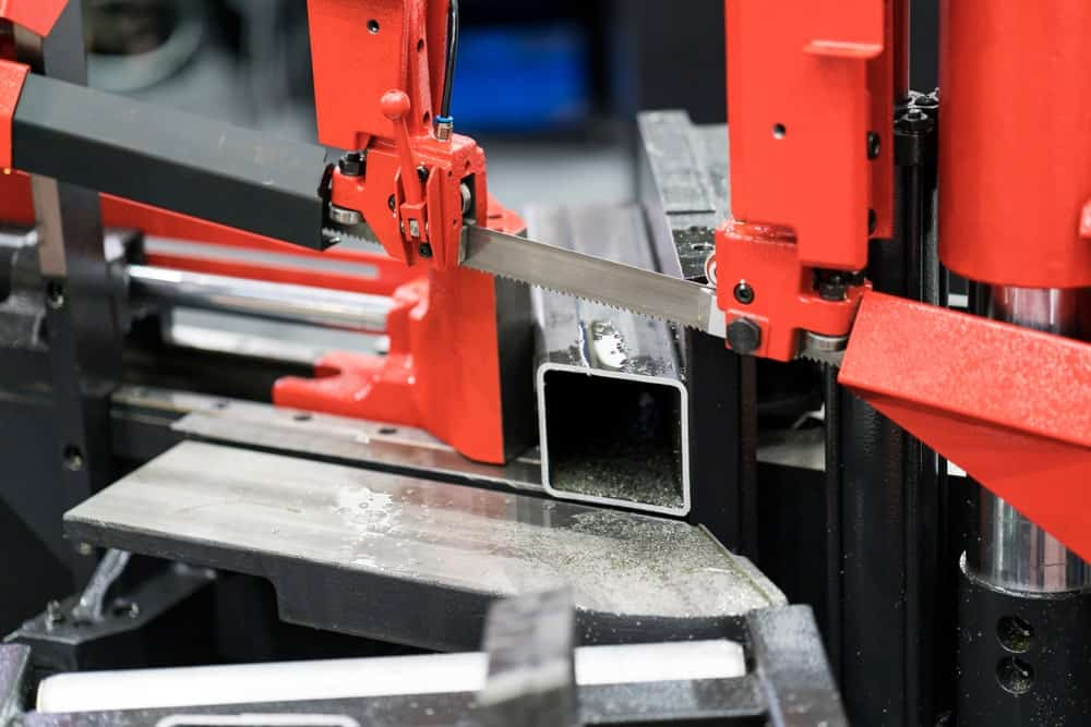 A close up shot of an automatic band saw about to cut a piece of metal bar.