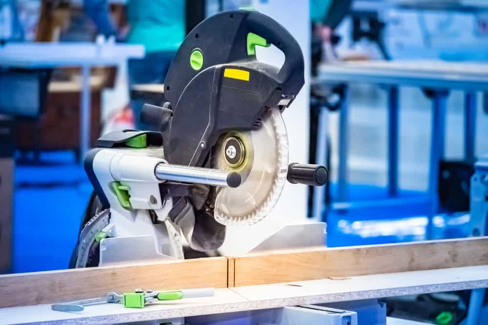 A piece of high tech circular saw equipment about to cut a piece of wood.