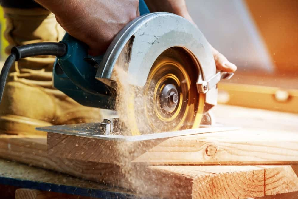 A handheld worm drive circular saw cutting a thick piece of wood in mid motion.