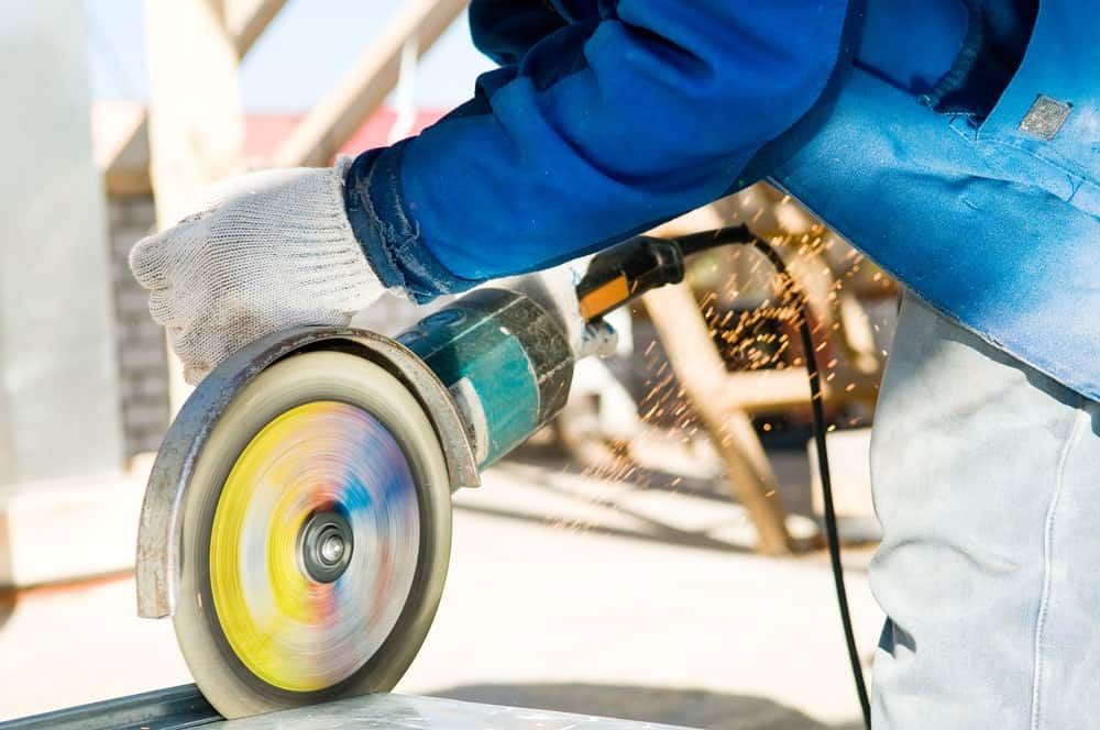 A carpenter using a heavy-duty hand held abrasive circular saw in mid motion.