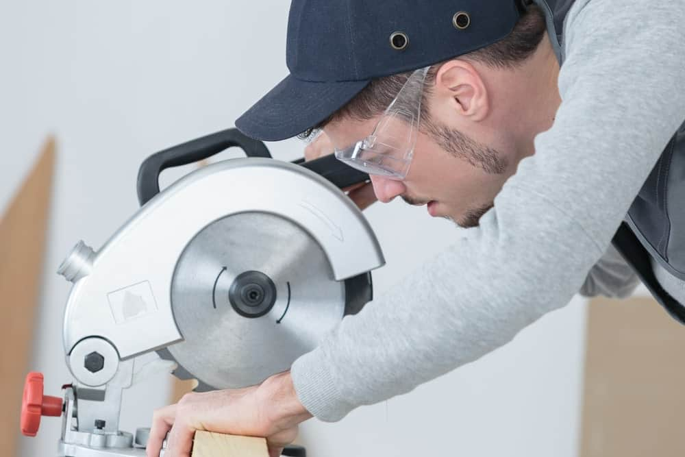 A carpenter in the motion of using a circular saw to cut the piece of wood he holds in place.