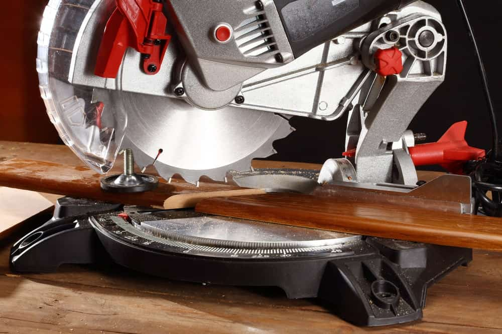 A piece of wood being cut by a mitre saw on a wood top platform.