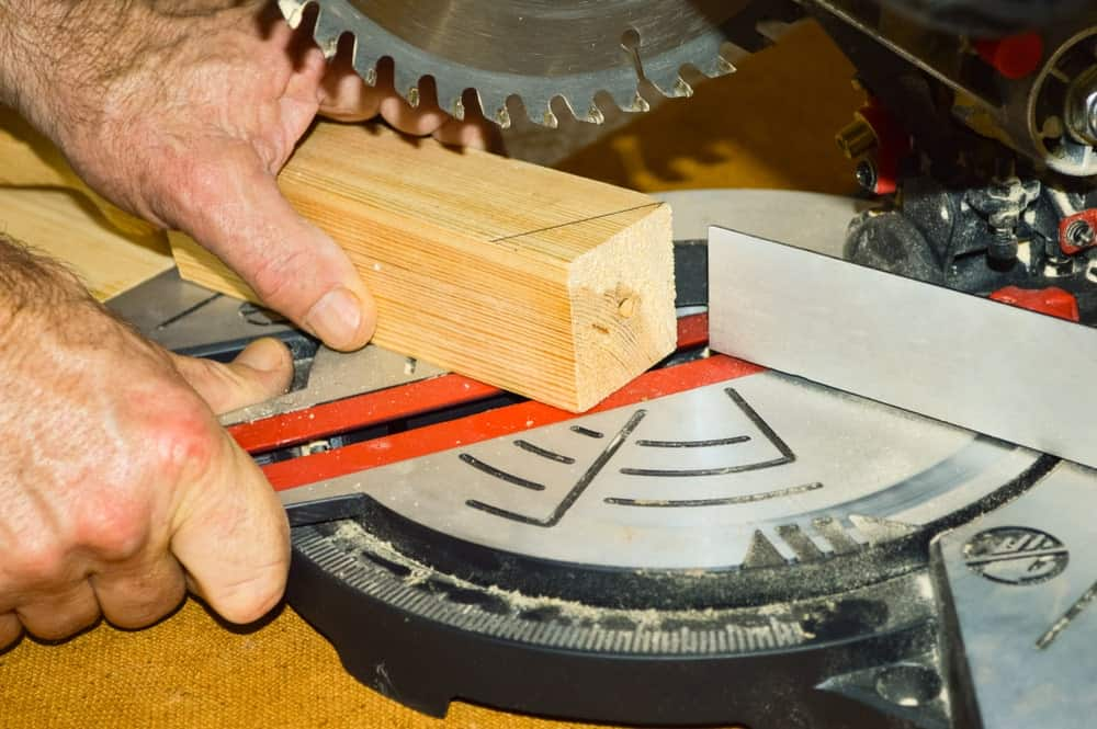 A piece of 2x2 wood being held in place to be cut by a mitre saw.
