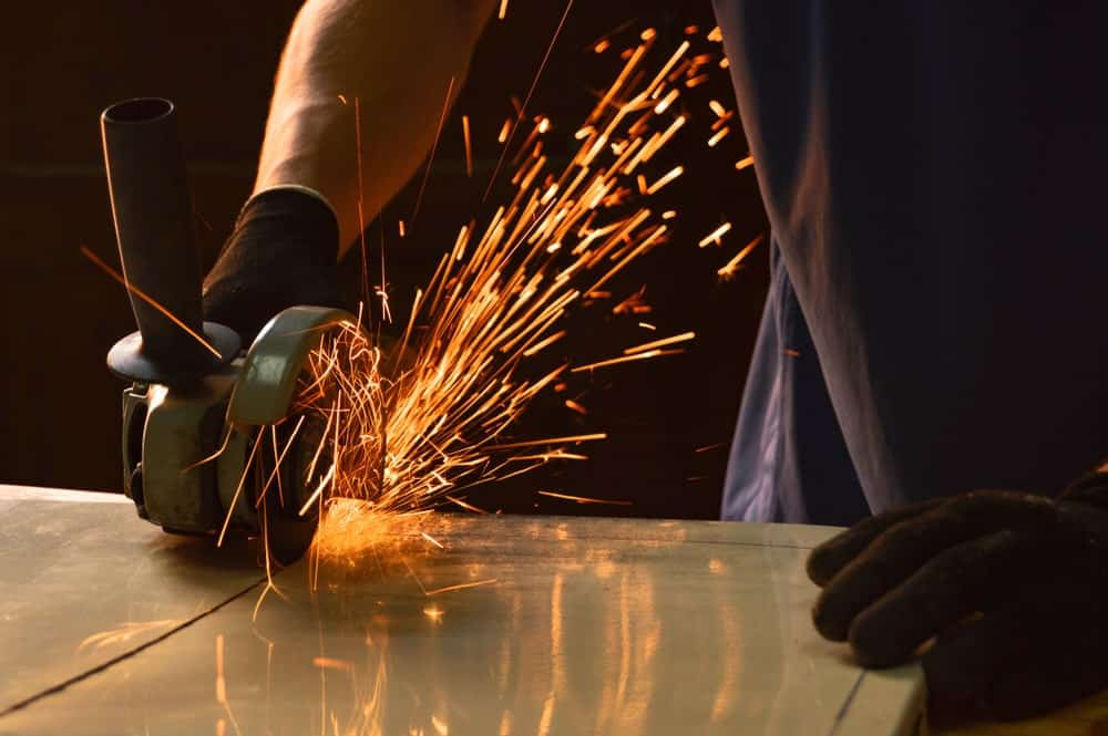 A close-up look at a radial saw in action with sparks flying.