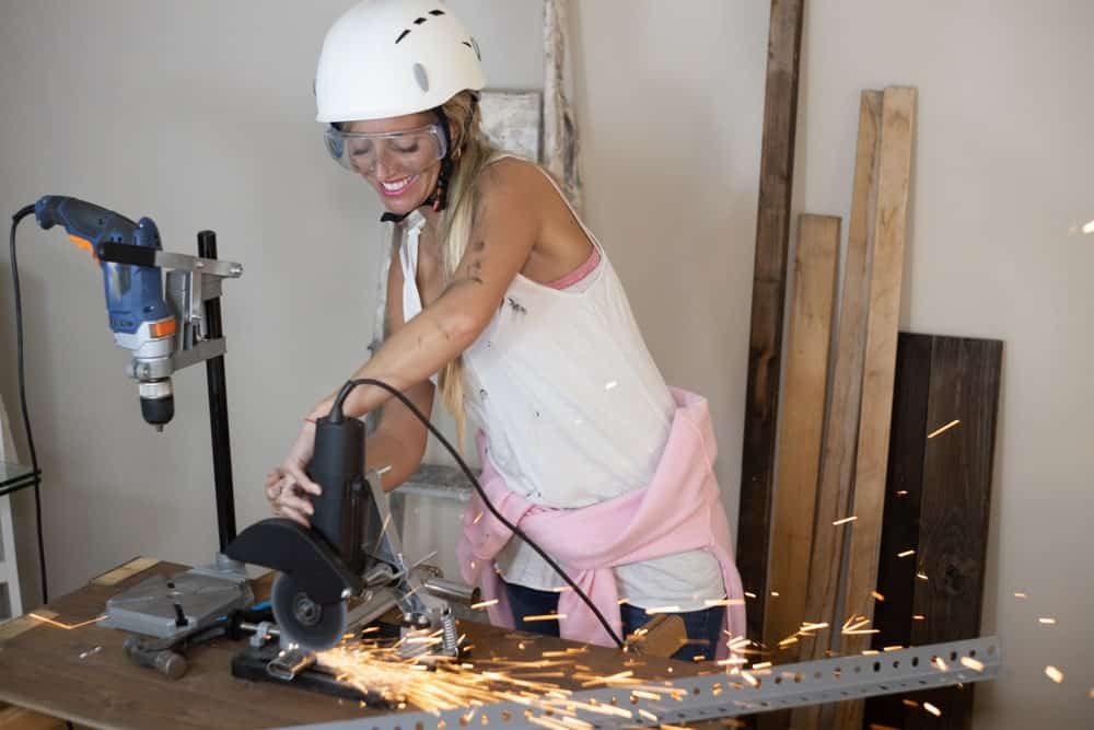 A female carpenter using a radial saw to cut up some pieces of metal.