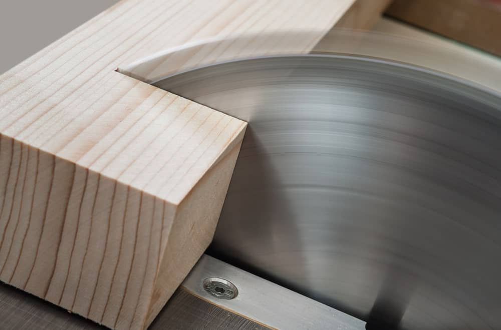 A photograph capture of a thick piece of beautiful wood being cut by a table saw.