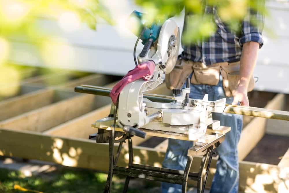 A carpenter using a table saw machine that is good for cutting long pieces of wood.