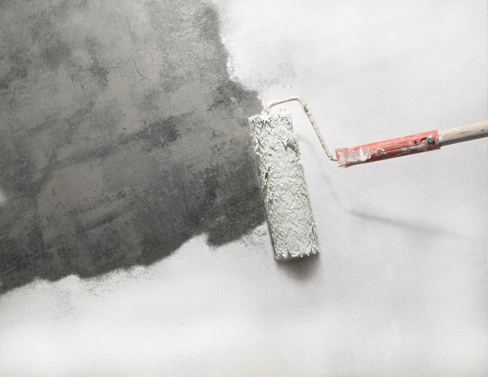 Paint roller applying white primer on a cement surface.