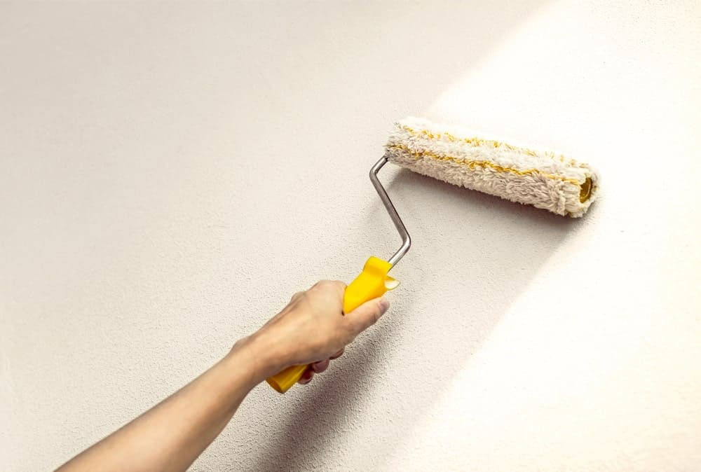 Paint roller applying coating on a wall.