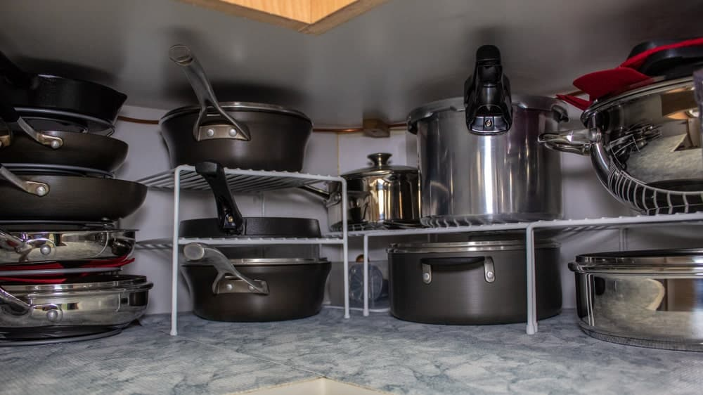 Pots and pans inside a cabinet.