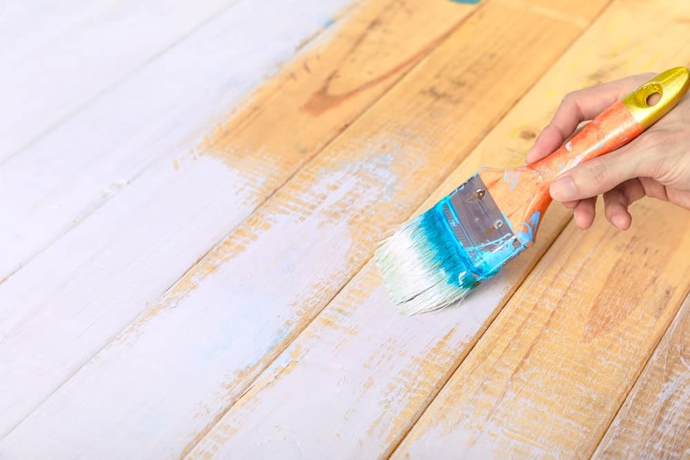 Applying white primer on a wooden surface.