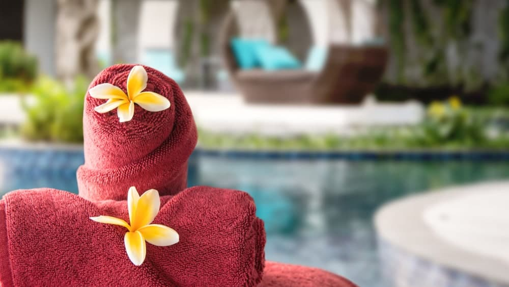 Rolled red towels topped with a flower petal on an outdoor resort setting.