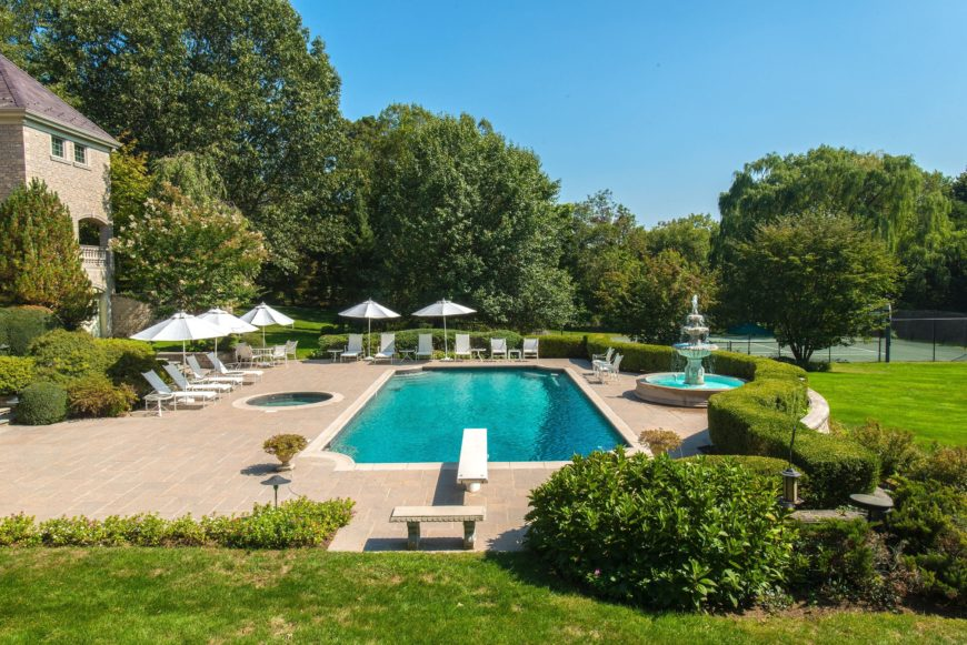 A look at the home's large outdoor swimming pool with lots of sitting lounges with umbrellas on the side. Images courtesy of Toptenrealestatedeals.com.
