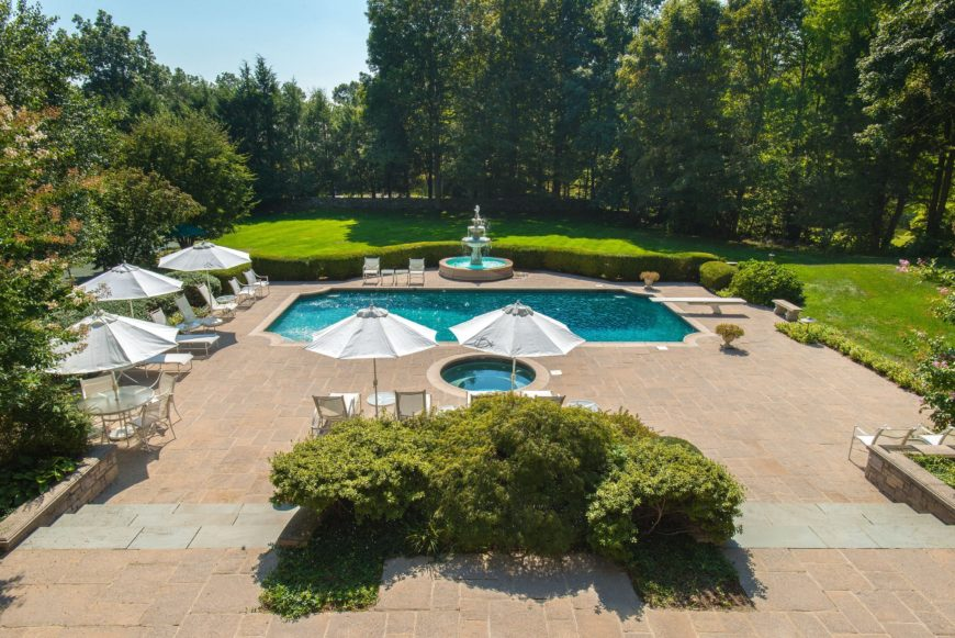 An aerial view of the property's outdoor area showcasing the large swimming pool with a fountain on the and is surrounded by several sitting lounges. Images courtesy of Toptenrealestatedeals.com.