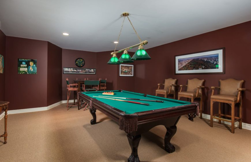 There are a man cave as well featuring brown walls and beige carpet flooring. There area bar area and a billiard table in the middle. Images courtesy of Toptenrealestatedeals.com.
