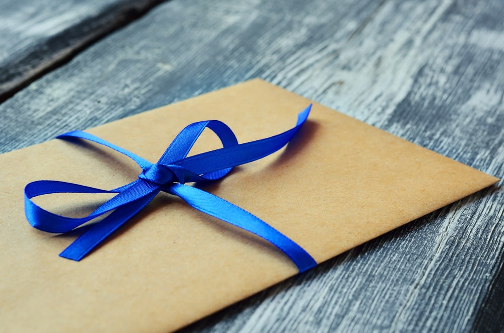 Kraft envelope tied with blue ribbon on a wooden background.