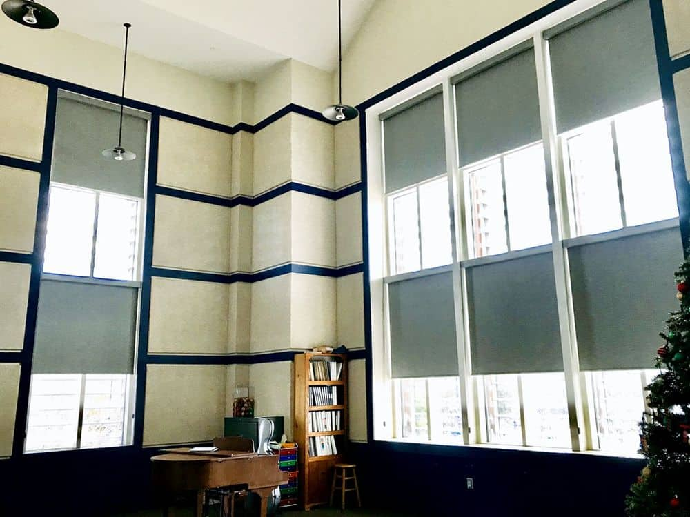 This room features stylish walls and a tall ceiling lighted by pendant lights. There are windows as well featuring window shades.