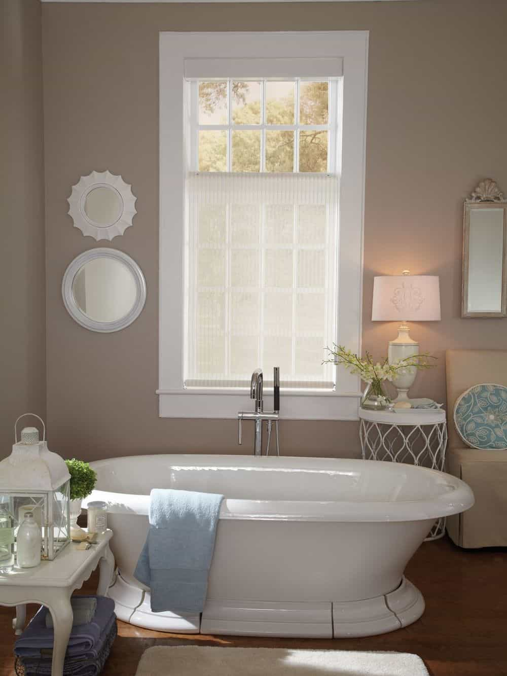 A primary bathroom featuring a freestanding tub and a side table with a charming table lamp, along with a window with a lovely window shade.
