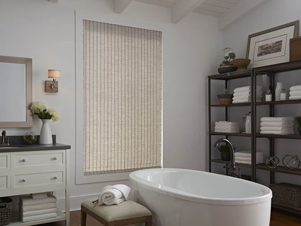 A primary bathroom featuring a freestanding tub and a classy sink counter, along with freestanding shelving on the side. The room also features a wooden ceiling with exposed beams.