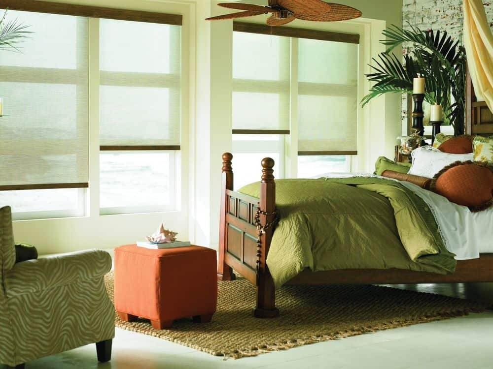 A primary suite boasting an elegant bed set and an olive green chair on the side. The room offers windows with roller window shades.