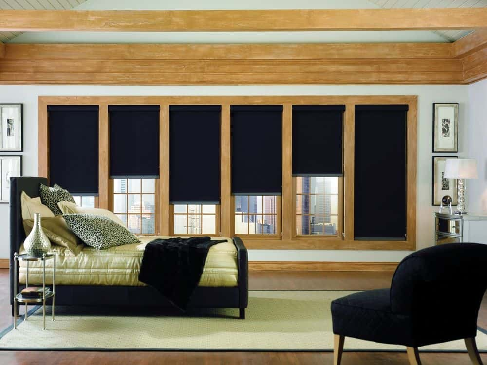 A primary suite boasting an elegant black bed set paired with a black chair and black window shades. The room has hardwood floors and a ceiling with beams.