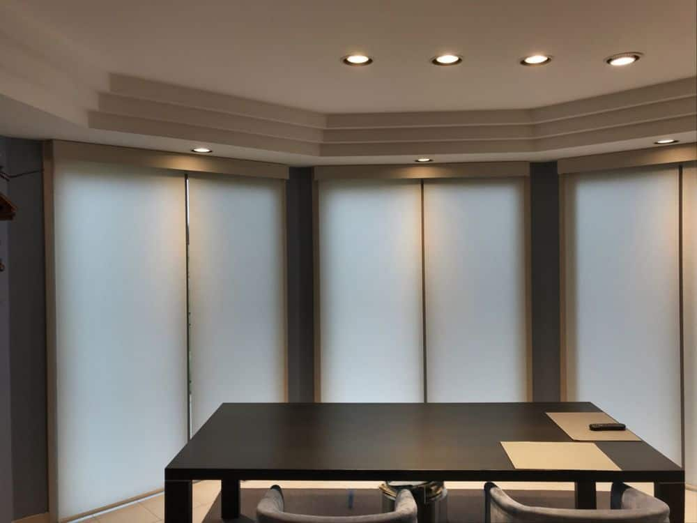 A dining room boasting a modern dining table and chairs set lighted by recessed ceiling lights on the stylish tray ceiling. The room also has large windows covered by window shades.