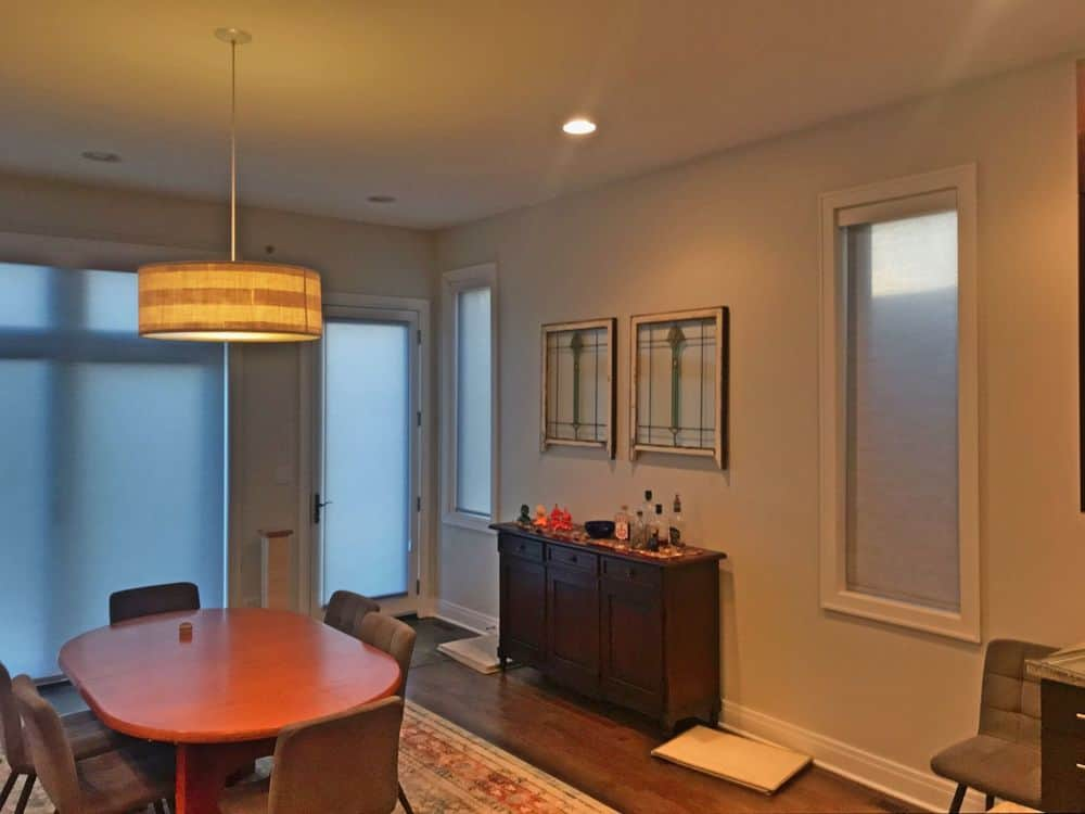 This dining room featuring a small dining table and chairs set for six, set on top of the area rug covering the hardwood flooring and is lighted by a classy ceiling light.